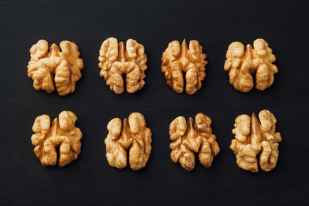 walnut: shelled walnuts in a row on black background