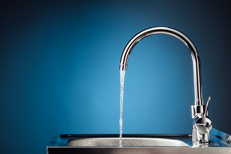 mixer tap with flowing water, blue background Foto de archivo