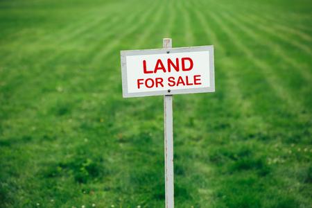 trimmed: land for sale sign against trimmed lawn background