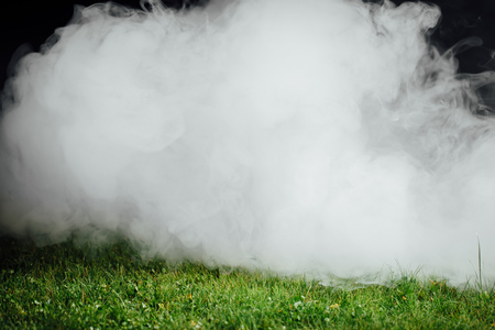 emit: smoke over the green grass lawn