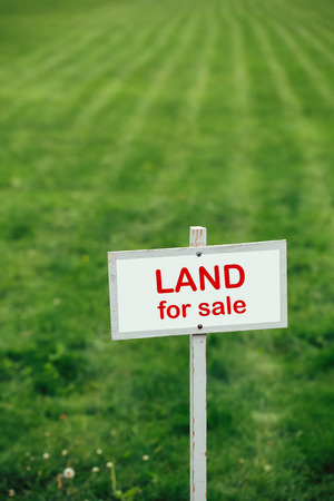 sale sign: land for sale sign against trimmed lawn background