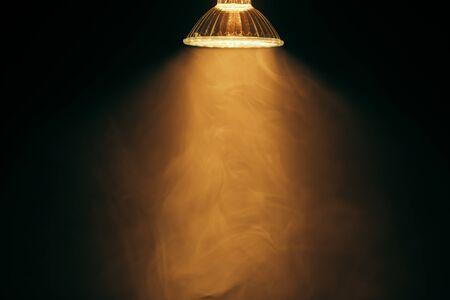 atmosfera: lámpara halógena con reflector, luz cálida en la niebla