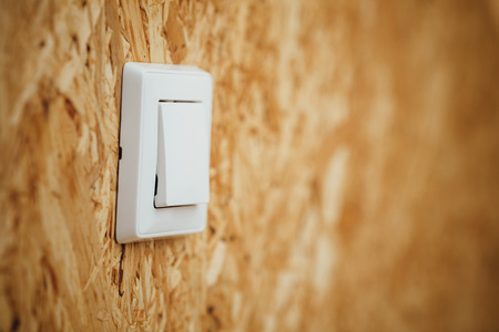 osb: electric light switch, wooden osb background with copy-space