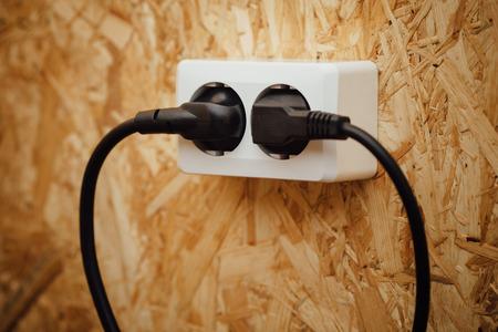 osb: AC power plug and socket, wooden osb wall background