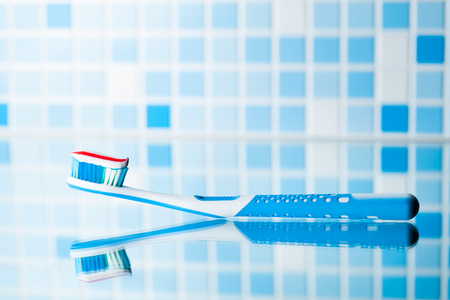 stomatological: toothbrush with red stripe toothpaste and mirror reflection