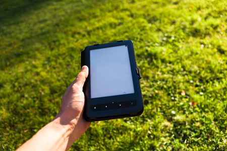e-Book reader in hand, green grass background Stock Photo