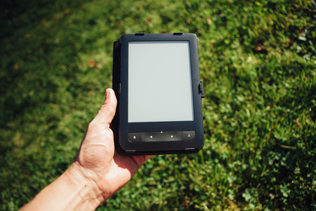 palm reading: e-Book reader in hand, green grass background Stock Photo