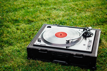 lp: turntable with LP vinyl record on green grass background