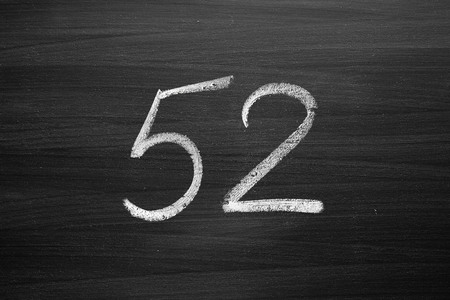 title hands: number fifty two enumeration written with a chalk on the blackboard Stock Photo