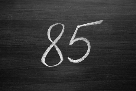 number eighty five enumeration written with a chalk on the blackboard Stock Photo