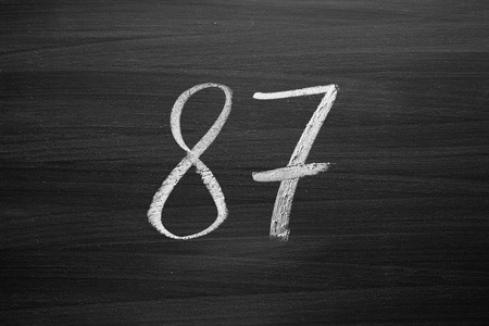 number eighty seven enumeration written with a chalk on the blackboard Stock Photo