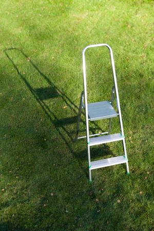 metallic stairs: ladder on green lawn background