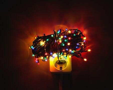 power concept: Christmas garland lights bundle on power socket, electricity concept