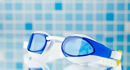 professional swimming glasses for training or competition, blue tile background