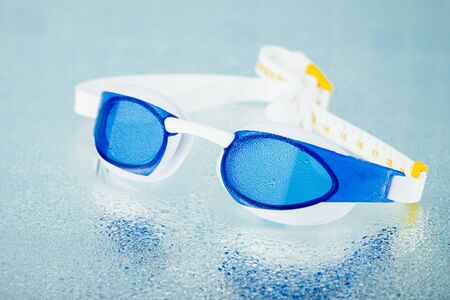 streamlining: professional swimming glasses for training or competition, blue background