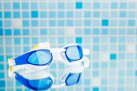streamlining: professional swimming glasses for training or competition, blue tile background
