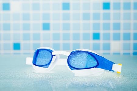 bathroom tiles: professional swimming glasses for training or competition, blue tile background