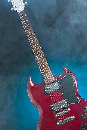 caoba: guitarra eléctrica en el humo, fondo azul