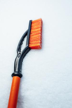 orange snow brush for car, snowflakes background Stock Photo