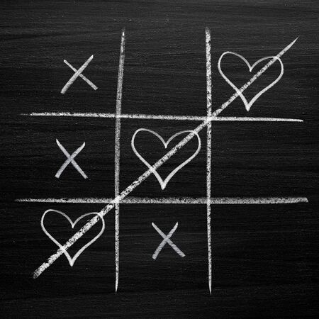 Tic tac toe game with chalk hearts, XO noughts and crosses Valentines Day style