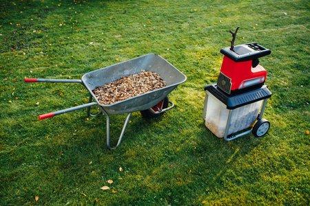 garden chipper, electric shredder (mulcher) with wheelbarrow full of wooden mulch, green grass background 版權商用圖片