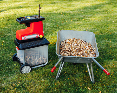 garden chipper, electric shredder (mulcher) with wheelbarrow full of wooden mulch, green grass background Stok Fotoğraf