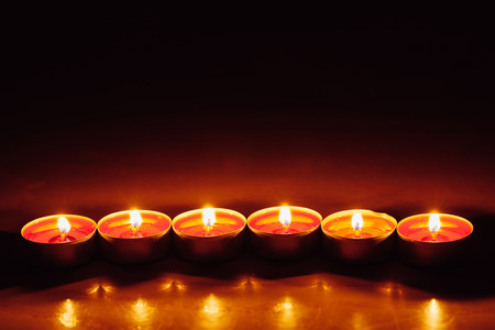 group of burning red tealight candles