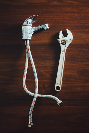 old faucet and adjustable wrench, plumbing repair concept