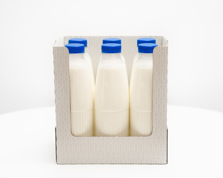milk bottles in cardboard box on white table