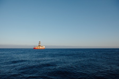 offshore oil and gas drillship, blue ocean background Фото со стока