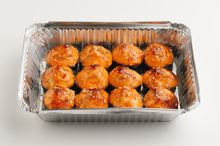 baked sushi rolls in a foil box container