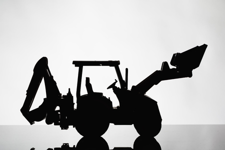 backhoe tractor silhouette on grey background