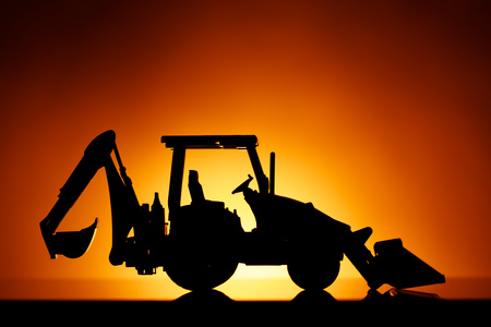 backhoe tractor silhouette, orange sunset background Фото со стока - 123075685