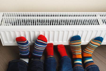 legs with colorful socks on heating radiator Фото со стока