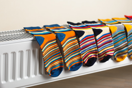 colorful socks are being drying on the radiator Фото со стока - 123075688