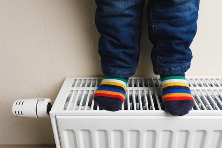 child feet with colorful socks on radiator