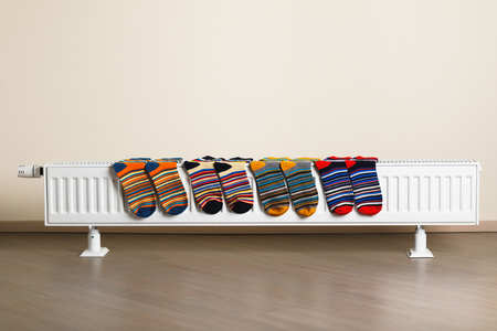 colorful socks are being drying on the radiator Фото со стока - 123075704