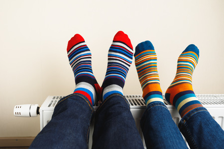 legs with colorful socks on heating radiator Фото со стока