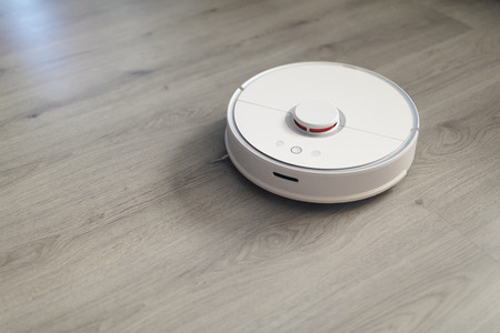 robotic vacuum cleaner on laminate floor in action Фото со стока