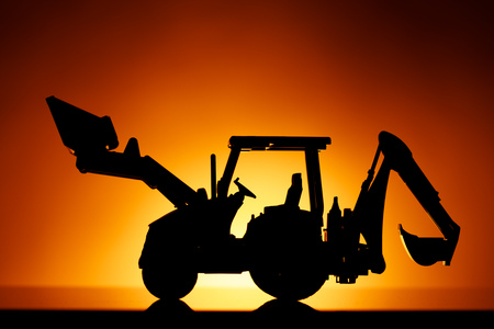 backhoe tractor silhouette, orange sunset background