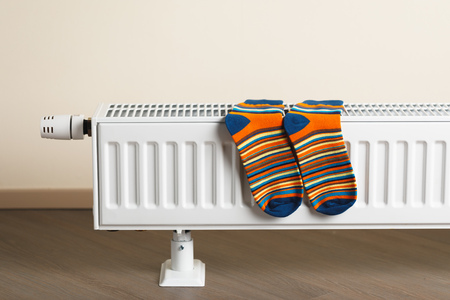 striped socks are being dry on the radiator Фото со стока