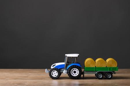 farm tractor toy with hay trailer, copy-space background Фото со стока