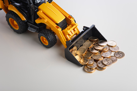 tractor rake up money coins with a bucket Фото со стока