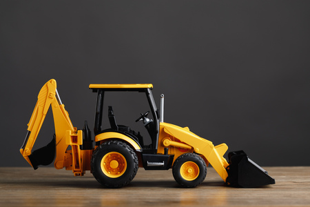backhoe tractor toy, gray background