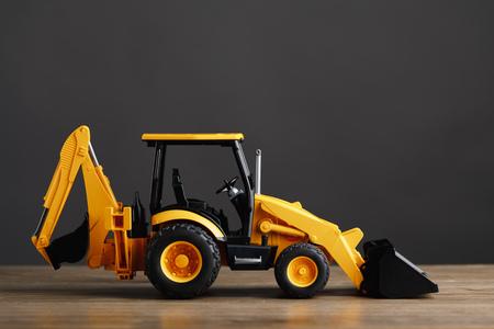 juguete tractor retroexcavadora, fondo gris