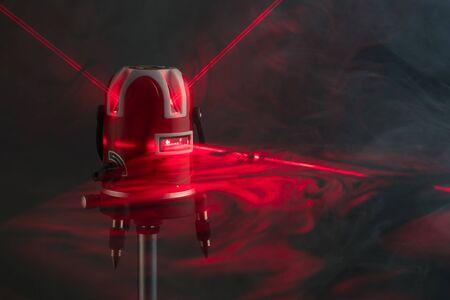 Herramienta de nivel láser rayos de luz roja en humo Foto de archivo