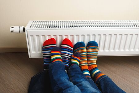 legs with colorful socks in front of heating radiator