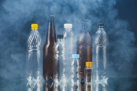 variety of plastic bottles in smoke, pollution concept