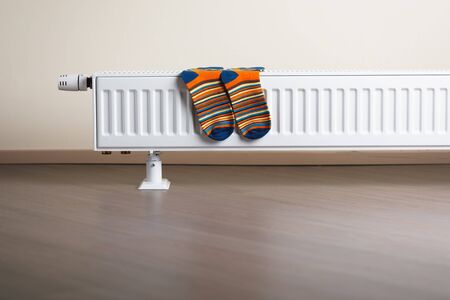 colorful socks are being dry on the radiator Stock Photo