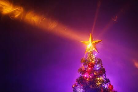 Árbol de Navidad con luces festivas, fondo morado Foto de archivo